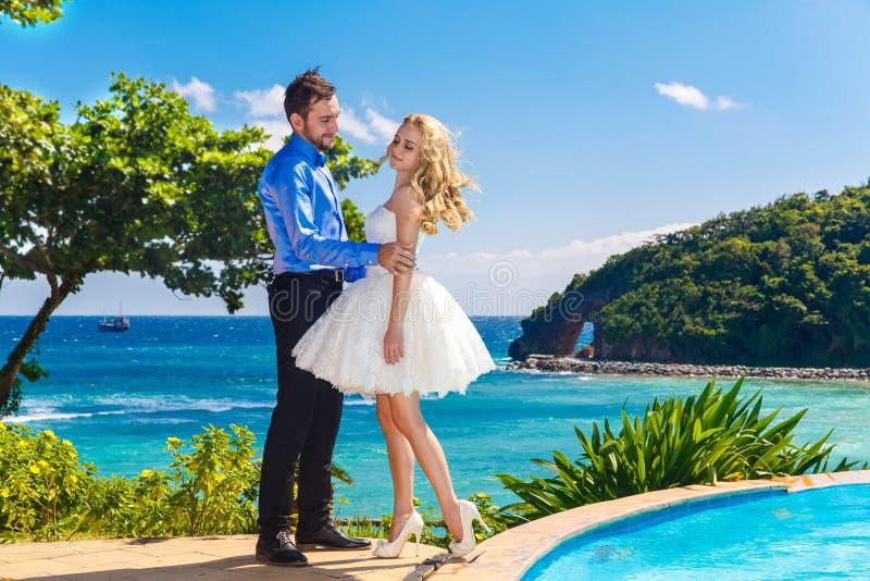 Jeunes mariés heureux ayant l'amusement sur une plage tropicale photo libre de droits