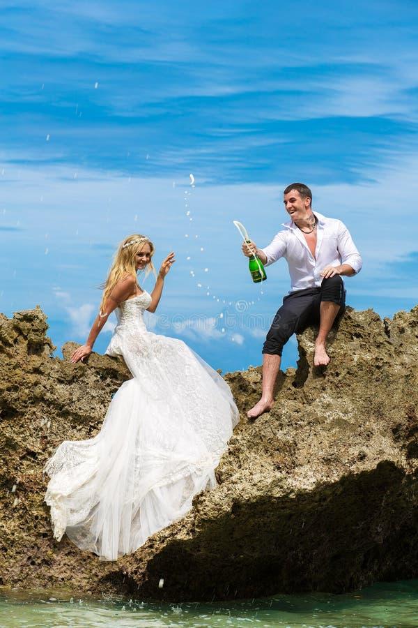 Jeunes mariés heureux ayant l'amusement sur une plage tropicale sous le p photo libre de droits
