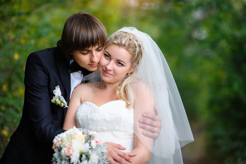 Jeunes mariés heureux de couples leur jour du mariage image stock