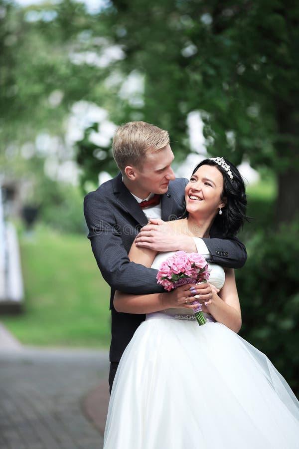 Jeunes jeunes mariés heureux dehors leur jour du mariage photos libres de droits