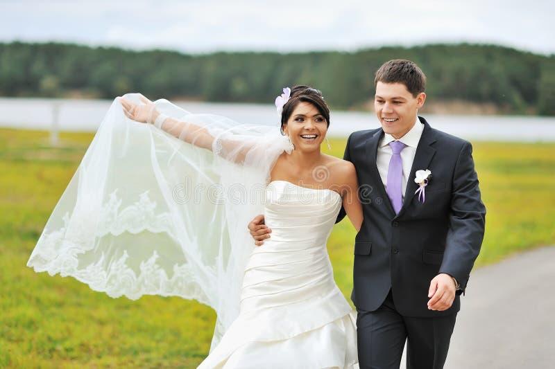 Jeunes mariés heureux marchant en parc photographie stock libre de droits
