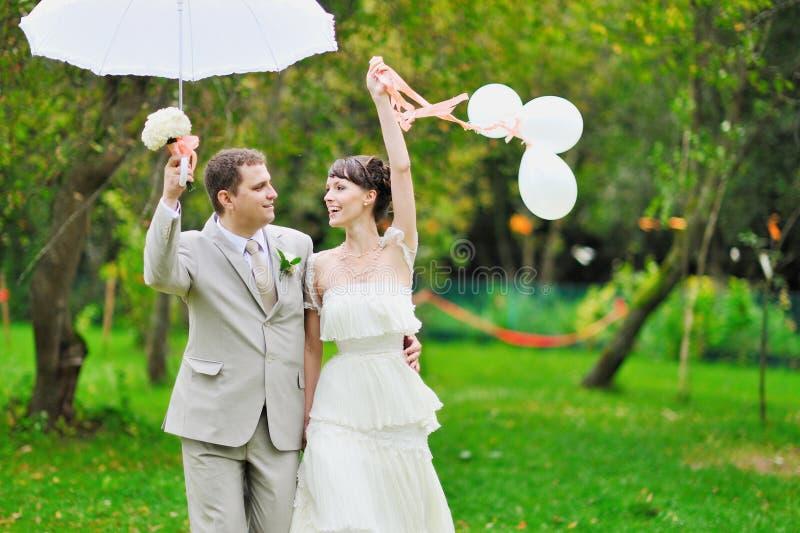 Jeunes mariés heureux marchant ensemble en stationnement photos libres de droits
