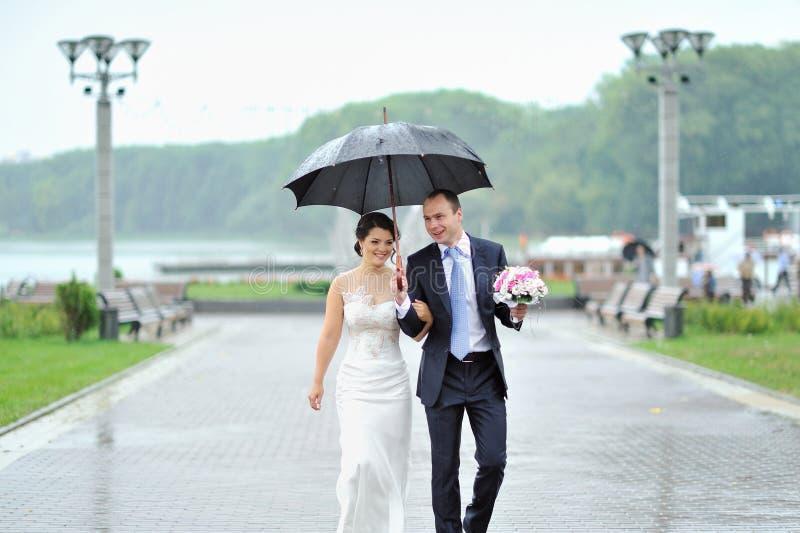 Jeunes mariés heureux marchant par la pluie leur jour du mariage photos libres de droits