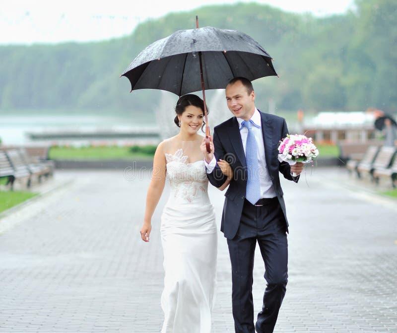 Jeunes mariés heureux marchant par la pluie leur jour du mariage photos stock