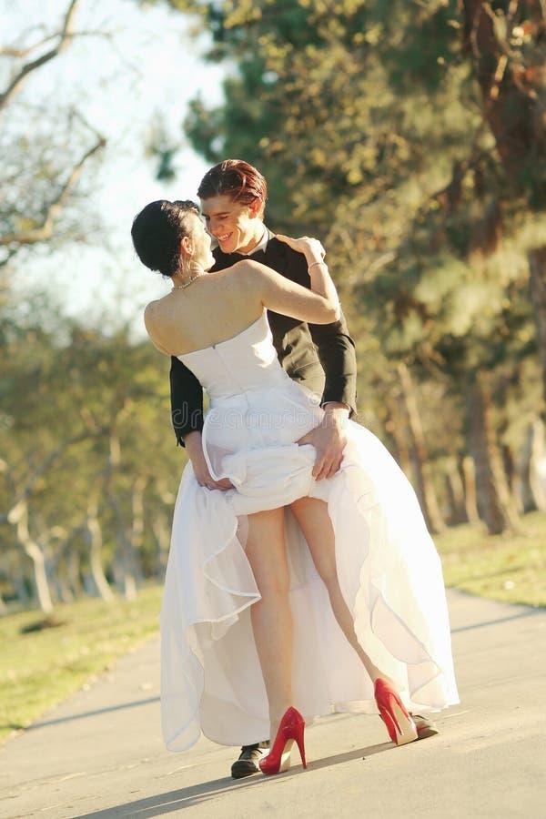 Jeunes mariés heureux Married Outdoors dans une forêt photo libre de droits