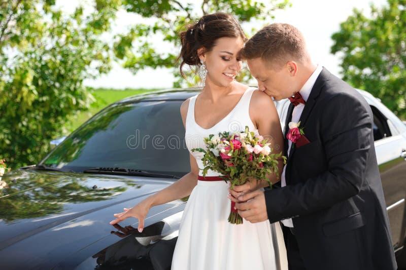 Jeunes mariés heureux près de voiture image stock