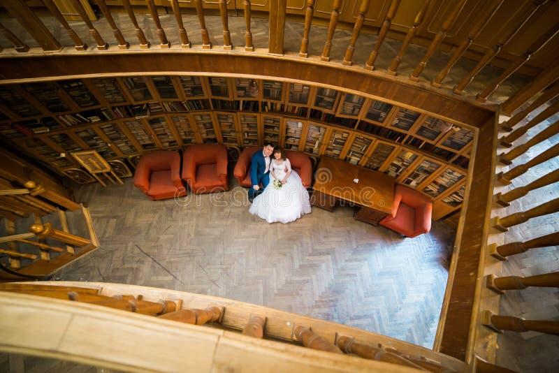 Jeunes mariés heureux se reposant sur le sofa rouge à la vieille bibliothèque La vue à partir du dessus images stock