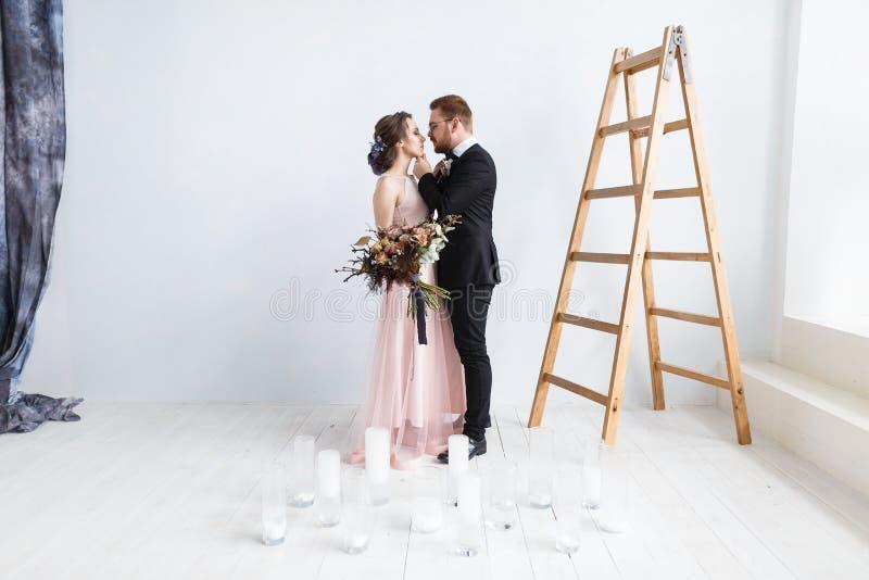 Jeunes mariés heureux sur l'échelle au studio image libre de droits