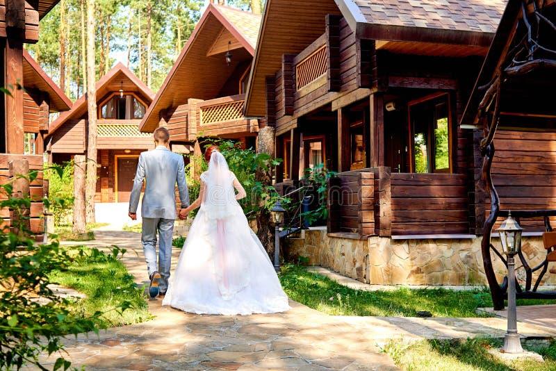 Jeunes mariés heureux tenant des mains et marchant près de la maison en bois en parc le jour du mariage, l'espace de copie Couple photos libres de droits