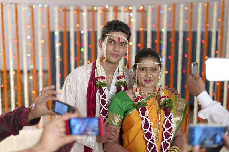 Jeunes mariés indous indiens étant tirés sur des mobiles dans le mariage de maharashtra. photos stock