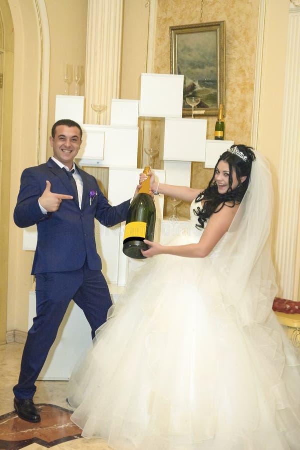 Jeunes mariés joyeux avec une grande bouteille de champagne images stock