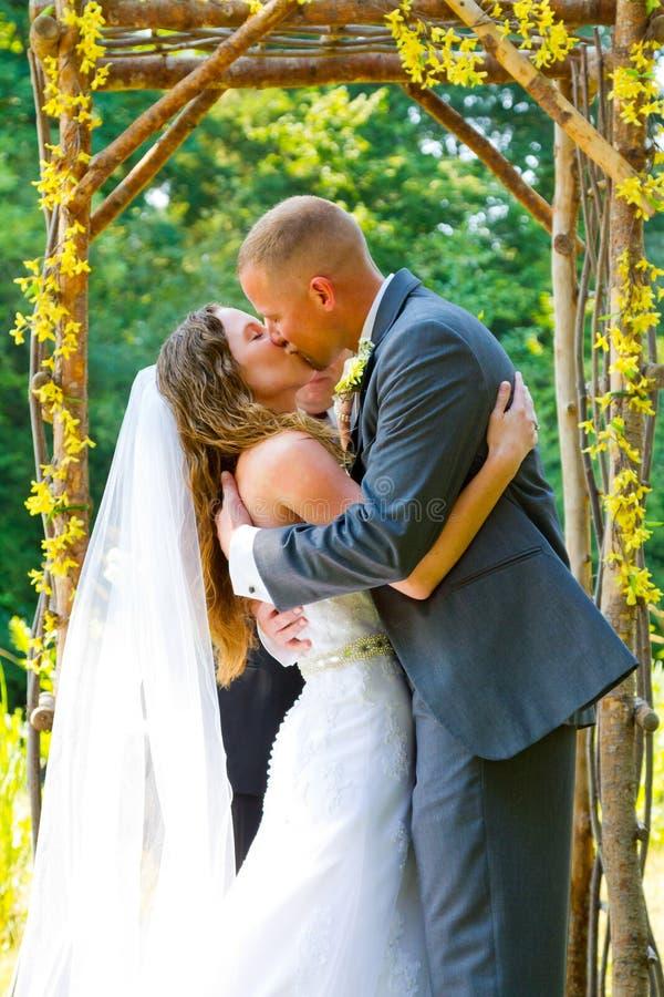 Jeunes mariés Kiss de cérémonie de mariage photos stock