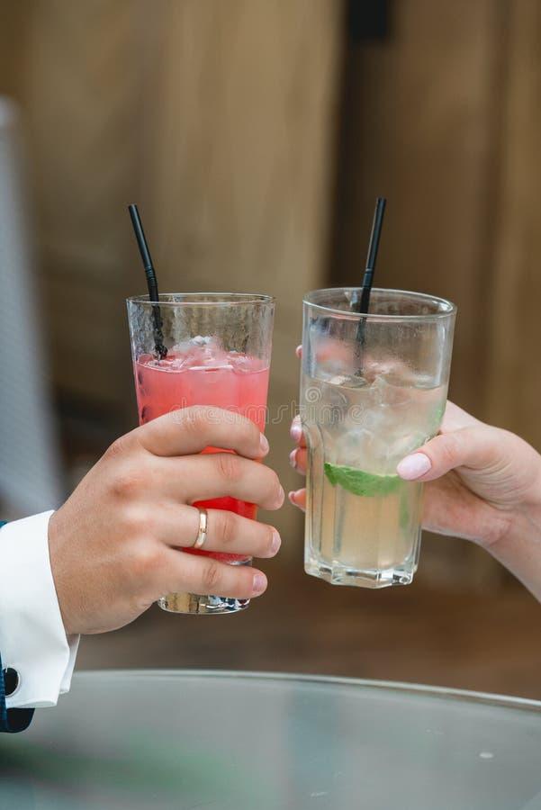 Jeunes mariés magnifiques grillant avec les cocktails alcooliques, jour du mariage Mains retenant des glaces images libres de droits