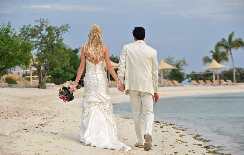 Jeunes mariés marchant ensemble sur la plage photos libres de droits