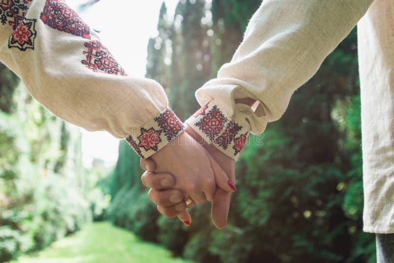 Jeunes mariés marchant ensemble tenant leurs mains image stock