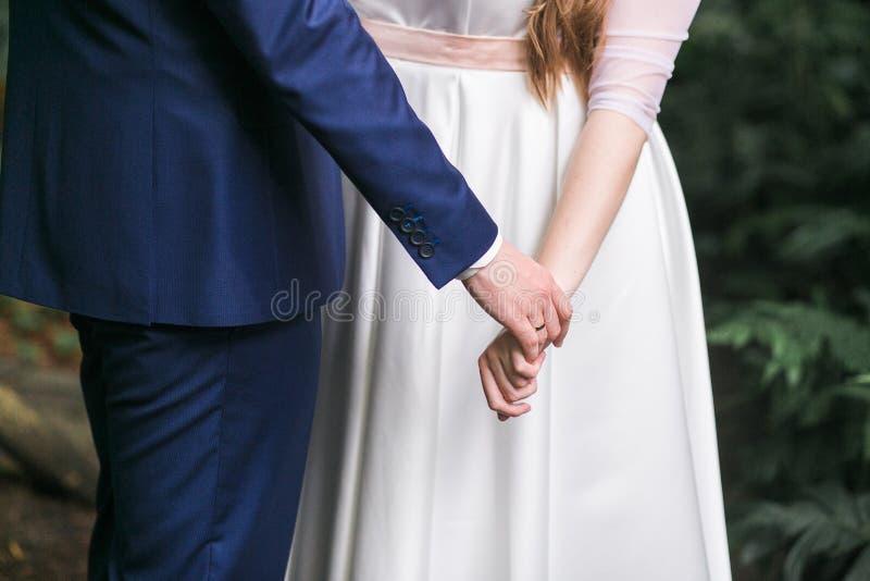 Jeunes mariés marchant ensemble tenant leurs mains Foyer en gros plan de tir sur des mains photographie stock