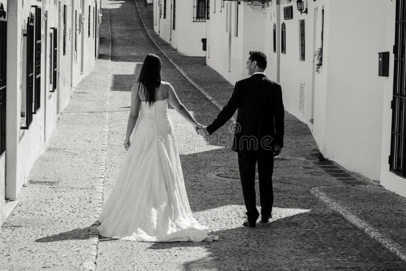 Jeunes mariés marchant le long de la rue photo libre de droits
