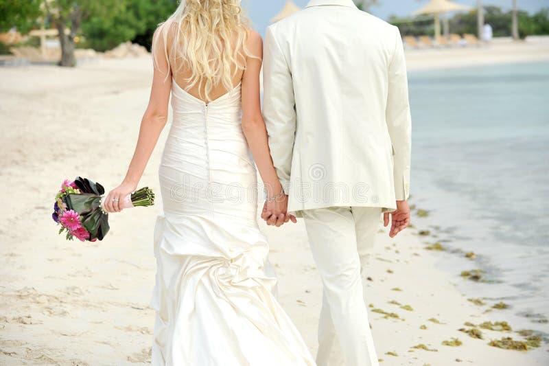 Jeunes mariés marchant main dans la main image stock