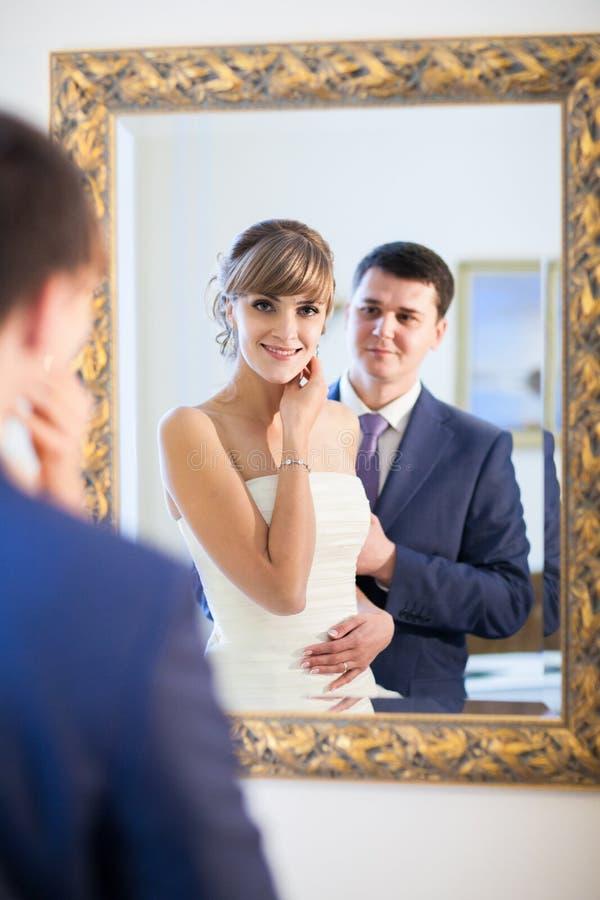 Jeunes mariés par le mirrir photo libre de droits