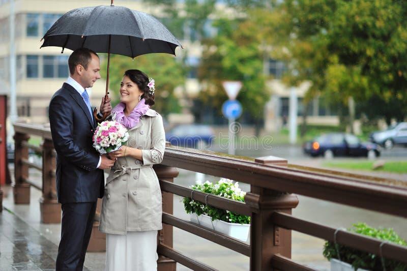 Jeunes mariés par temps pluvieux image stock
