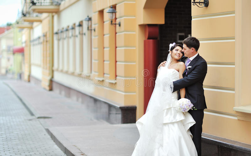 Jeunes mariés posant dans une vieille ville - couple de mariage photo libre de droits