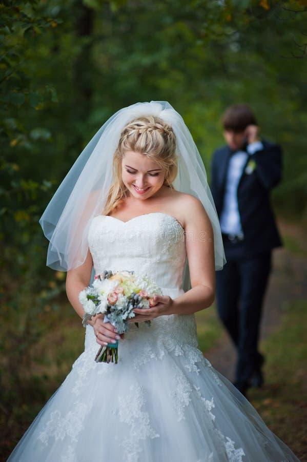 Jeunes mariés posant ensemble dehors photo stock