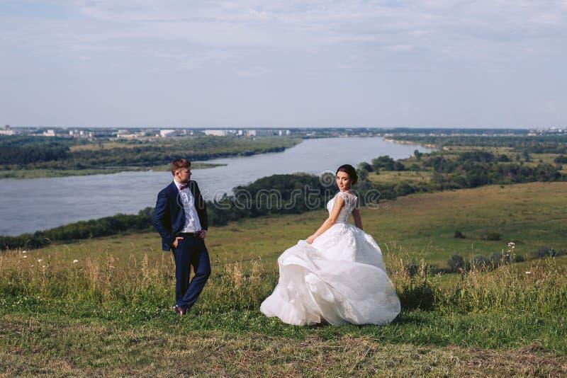 Jeunes mariés posant sur la nature leur jour du mariage photo stock