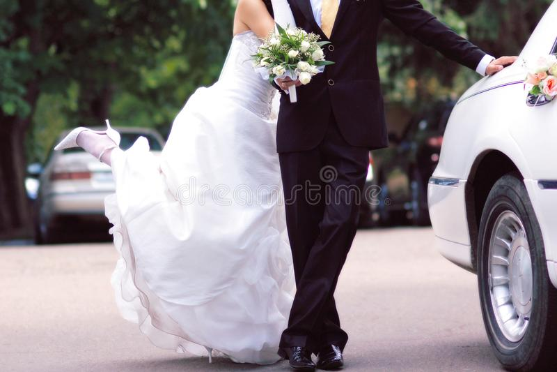 Jeunes mariés près de la limousine blanche, joyeuse images stock