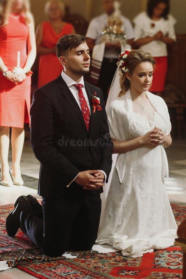 Jeunes mariés priant à la cérémonie de mariage dans l'église, belle image stock