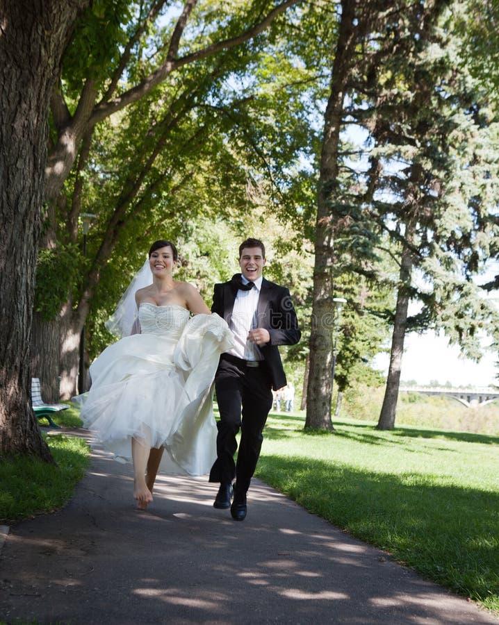 Jeunes mariés Running photographie stock