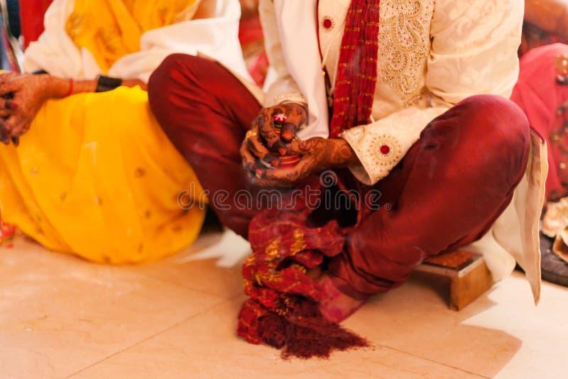 Jeunes mariés s'asseyant ensemble pour le puja, rituels indous typiques de mariage d'A photo libre de droits