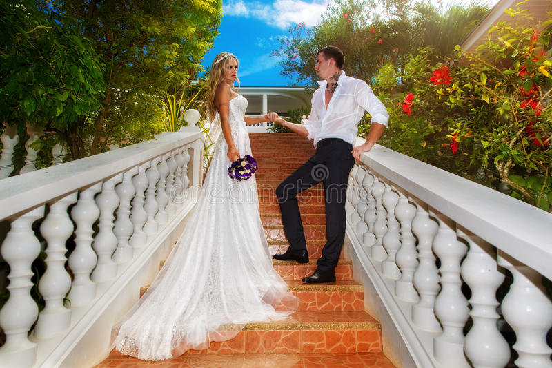 Jeunes mariés se tenant sur les escaliers dans l'hôtel sur un tropica photos stock