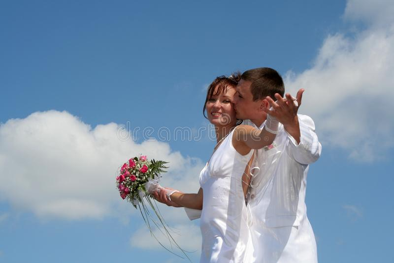 Jeunes mariés sur le fond de ciel bleu image libre de droits