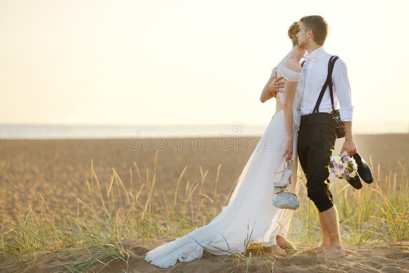 Jeunes mariés sur une plage au coucher du soleil photographie stock libre de droits