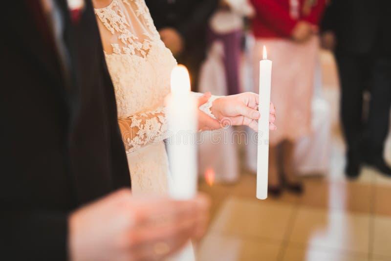 Jeunes mariés tenant des bougies dans l'église image libre de droits