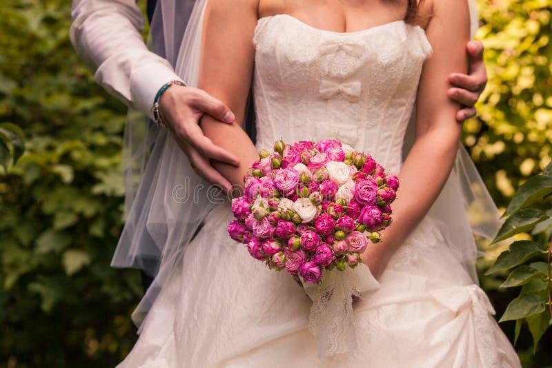 Jeunes mariés tenant la fin nuptiale de bouquet image stock