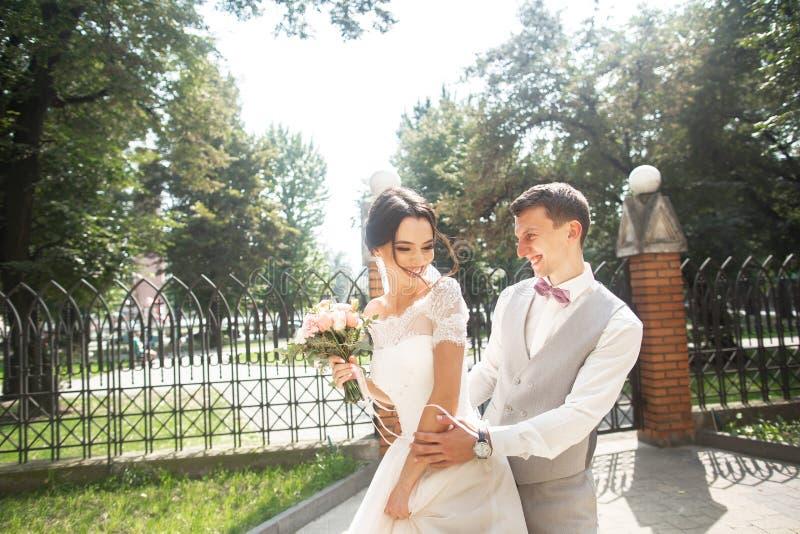 Jeunes mari?s au jour du mariage marchant en beau parc, extr?mit? de sourire s'amusant photo stock