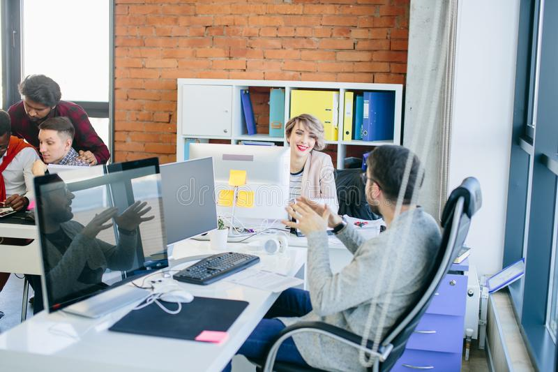 Jeunes membres de l'équipe beaux discutant des idées d'affaires dans le bureau image stock