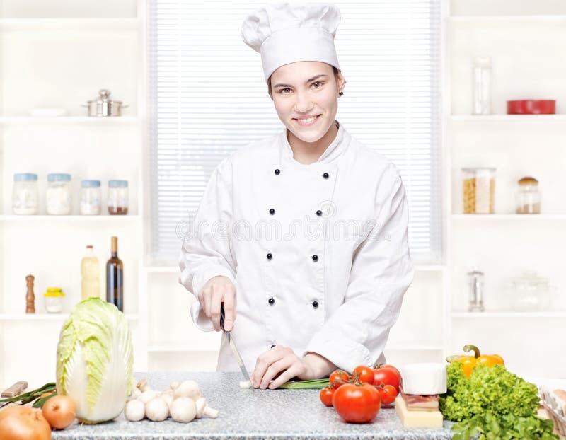 Jeunes oignons de découpage de chef dans la cuisine photo libre de droits