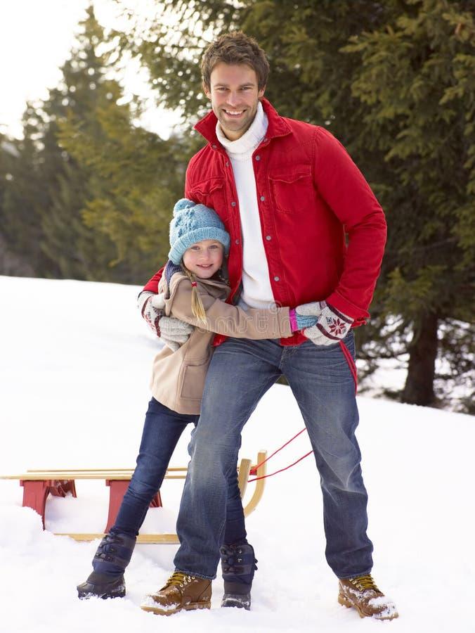 Jeunes père et descendant dans la neige avec le traîneau photographie stock libre de droits