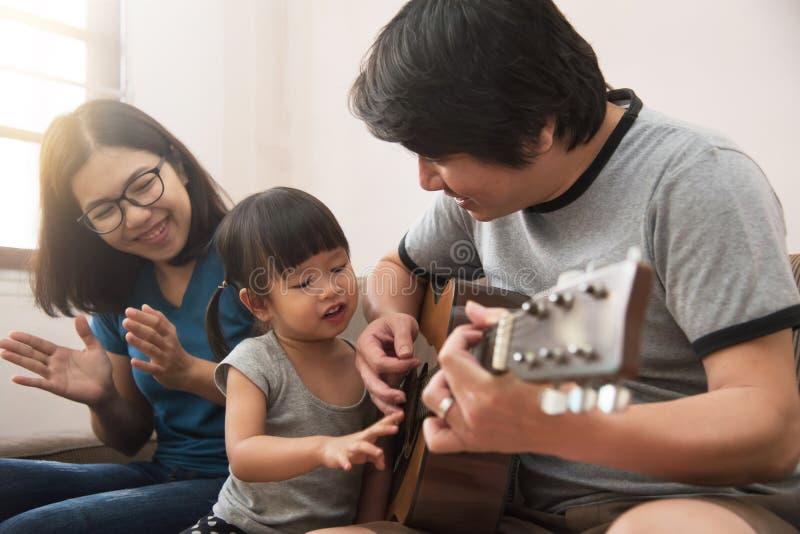 Jeunes père, mère asiatique et fille jouant le toget de guitare photos libres de droits