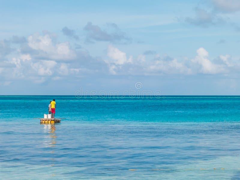 Jeunes pêcheurs avec la mer et le ciel bleus clairs photo stock