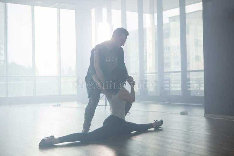 Jeunes paires de danseurs pratiquant à plusieurs reprises dans leur classe de danse image stock