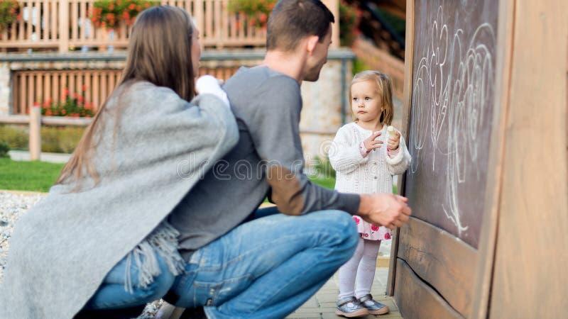 Jeunes parents avec leur dessin mignon de petite fille sur le tableau noir Enfant tenant la craie et le dessin photos stock