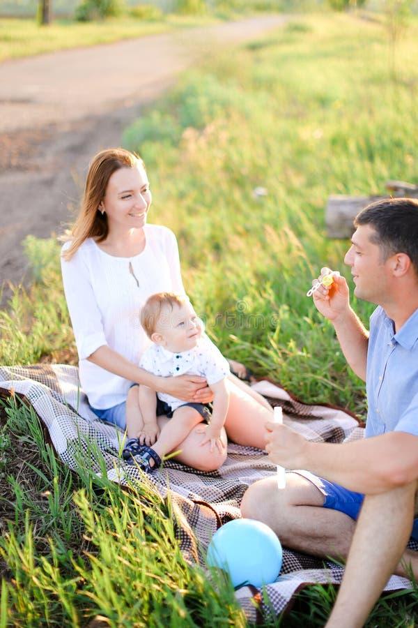 Jeunes parents caucasiens sittling sur l'herbe avec peu de bébé et bulles de soufflement images stock