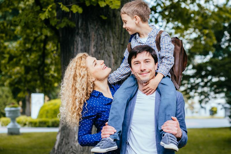 Jeunes parents disant au revoir à leur petit enfant près de l'école extérieure Père, mère et petit fils d'élève ayant nouveau image stock
