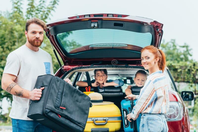 jeunes parents emballant le bagage dans le tronc de la voiture avec le regard d'enfants image libre de droits