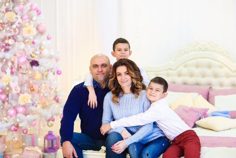 Jeunes parents heureux s'asseyant avec des fils près de l'arbre de sapin sur le lit photos libres de droits