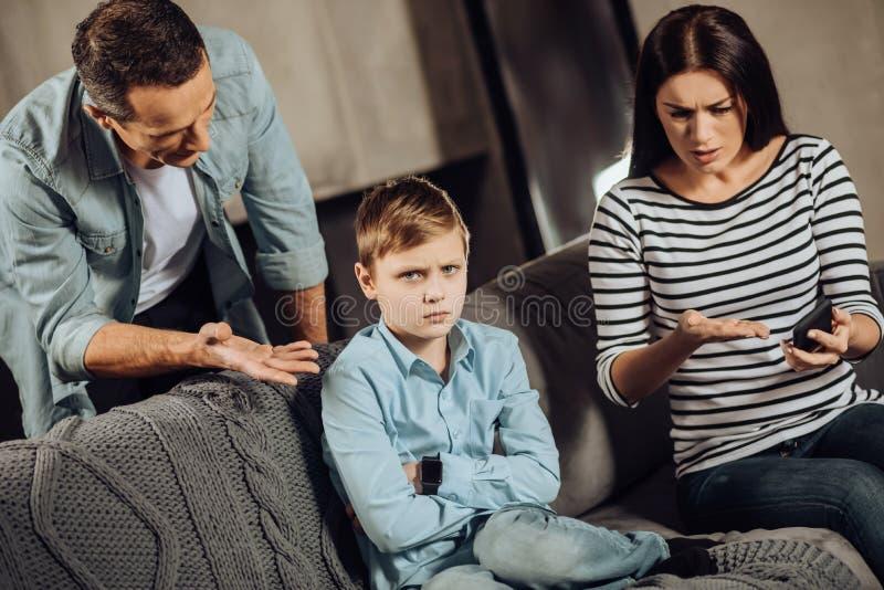 Jeunes parents instruisant leur fils offensé images stock