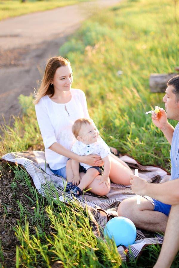 Jeunes parents sittling sur l'herbe avec peu de bébé et bulles de soufflement photo stock